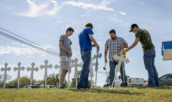 Jacob Kubena, from left, and his brother Zachary, Doug John and his son Shelby John set up a memorial of 26 metal crosses near First Baptist Church in Sutherland Springs on Monday, Nov. 6, 2017.