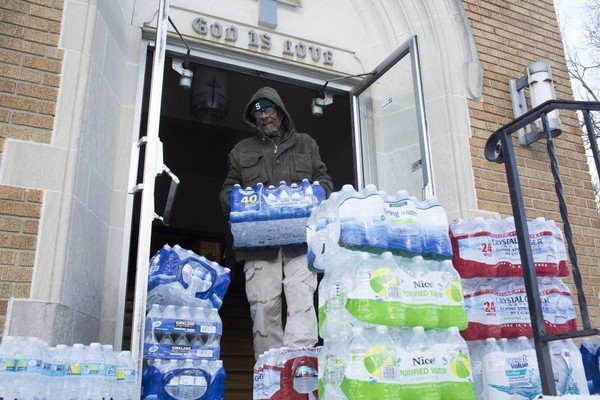 Maurice Rice organizes cases of water at the Joy Tabernacle Church on Monday, Jan. 11, 2016, in Flint.
