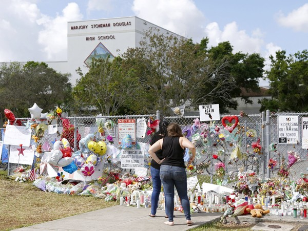 Mourners pay tribute at a memorial for the victims of the shooting at Marjory Stoneman Douglas High School on Sunday, Feb. 25, 2018, in Parkland, Fla. (David Santiago/Miami Herald via AP)