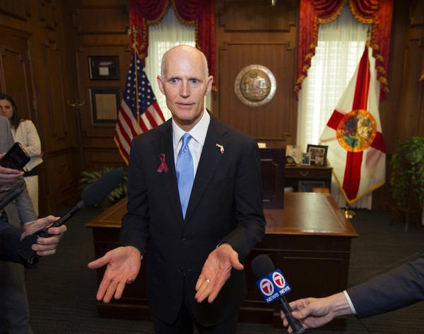 Florida Gov. Rick Scott talks to the media in his office after signing the Marjory Stoneman Douglas Public Safety Act at the Florida Capital in Tallahassee, Fla., Friday, March 9, 2018.