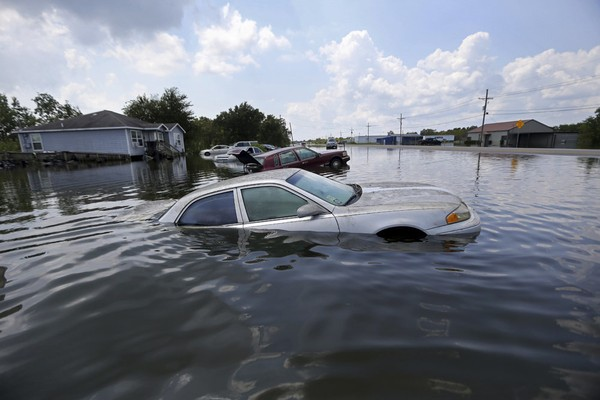 Flooded cars sit alongside a roadway in the aftermath of Tropical Storm Harvey, in Port Arthur, Texas, Saturday, Sept. 2, 2017.
