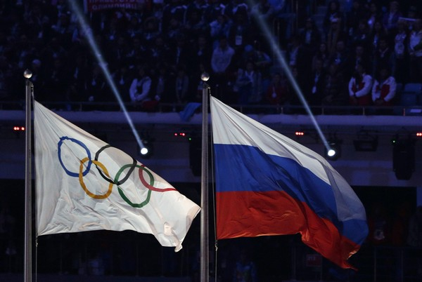 In this Feb. 23, 2014 file photo, the Russian national flag, right, flies after next to the Olympic flag during the closing ceremony of the 2014 Winter Olympics in Sochi, Russia. (AP Photo/Matthias Schrader, File)