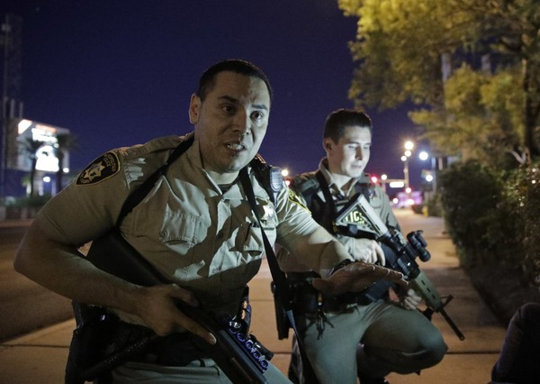 Police officers advise people to take cover near the scene of a shooting near the Mandalay Bay resort and casino on the Las Vegas Strip on Sunday, Oct. 1, 2017, in Las Vegas.
