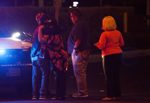 People embrace after arriving at Metro Headquarters to check on loved ones early Monday after a mass shooting at a music festival on the Las Vegas Strip on Sunday.