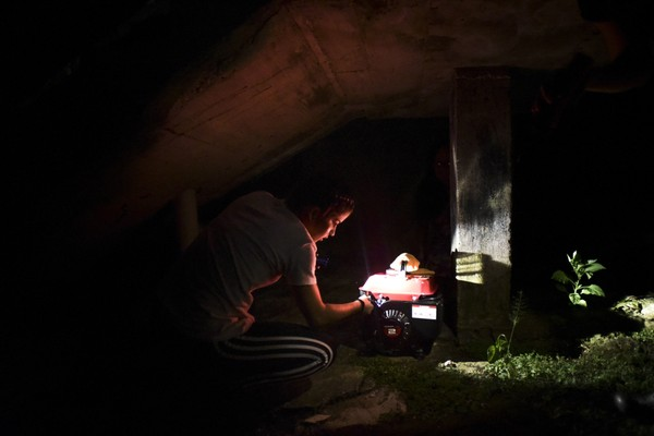 In this Dec. 21, 2017, photo, Barrio Patron resident Karina Santiago Gonzalez works on a small power plant in Morovis, Puerto Rico.