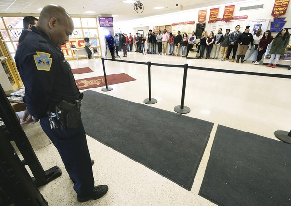 In this March 14, 2018, file photo, police patrolman John Burgette, 53, a school resource officer for 18 years, bows his head as Scranton High School students stand in silence to protest gun violence for 17 minutes at the high school in Scranton, Pa. (Butch Comegys / AP)