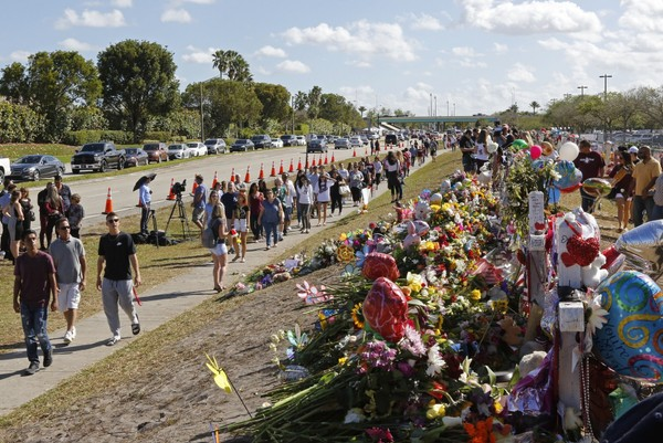 Parents and students walk by the memorial for the victims of the shooting at Marjory Stoneman Douglas High School on Sunday, Feb. 25, 2018. (David Santiago/Miami Herald via AP)