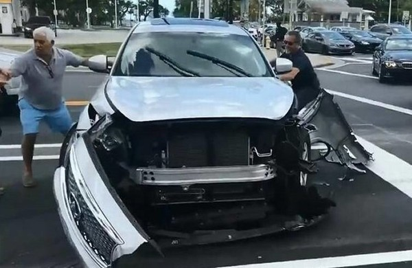 A screen shot from a bystander's video obtained by a Miami TV station shows two men attempting to stop the vehicle of an alleged hit-and-run driver trying to leave the scene early Sunday, March 11, 2018.