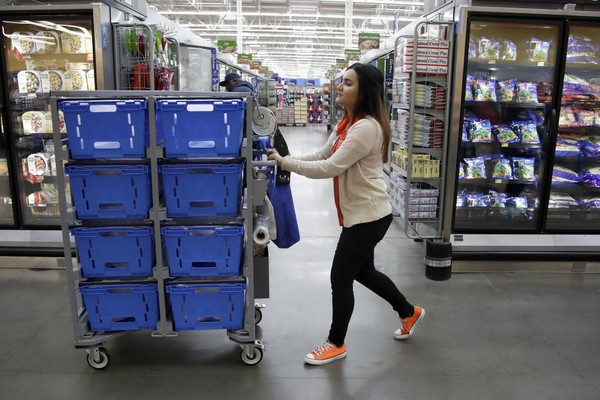 In this Thursday, Nov. 9, 2017, photo, Laila Ummelaila, a personal shopper at the Walmart store in Old Bridge, N.J., pushes a cart with bins as she shops for online shoppers. (AP Photo/Julio Cortez)