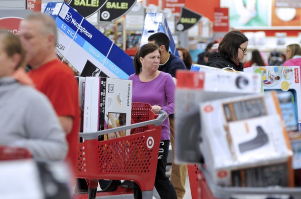 A woman maneuvers her way through Black Friday shoppers at the Target store in Plainville, Mass., shortly after the store opened. (Mark Stockwell/The Sun Chronicle via AP)
