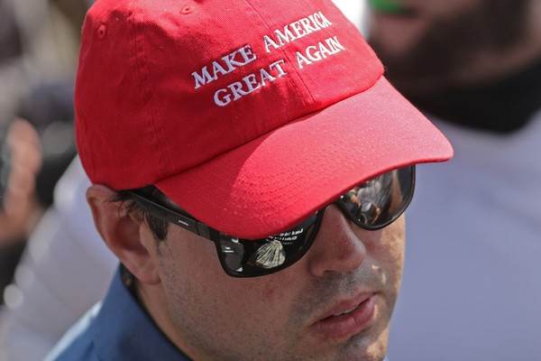 "In this Aug. 12, 2017, file photo, a man wears a ""Make America Great Again"" hat during a rally in Charlottesville, Virginia.  (Chip Somodevilla/Getty Images)"