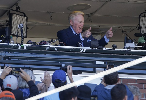 Los Angeles Dodgers announcer Vin Scully gestures to fans during the seventh inning stretch of a baseball game between the San Francisco Giants and the Dodgers in San Francisco, Saturday, Oct. 1, 2016. (AP Photo/Jeff Chiu, File)