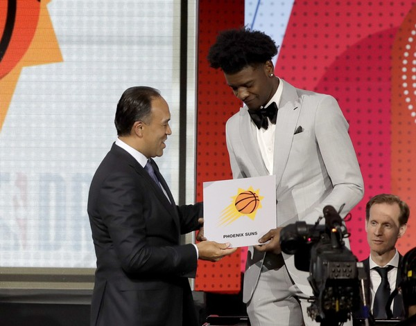 NBA Deputy Commissioner Mark Tatum, left, congratulates Phoenix Suns forward Josh Jackson after Tatum announced that the Suns had won the first pick for the NBA basketball draft, during the draft lottery Tuesday, May 15, 2018, in Chicago. (AP Photo/Charles Rex Arbogast)