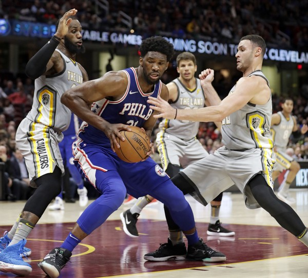 Philadelphia 76ers' Joel Embiid, center, dribbles against Cleveland Cavaliers' LeBron James and Larry Nance Jr. in the second half of an NBA basketball game, Thursday, March 1, 2018, in Cleveland. (AP Photo/Tony Dejak)