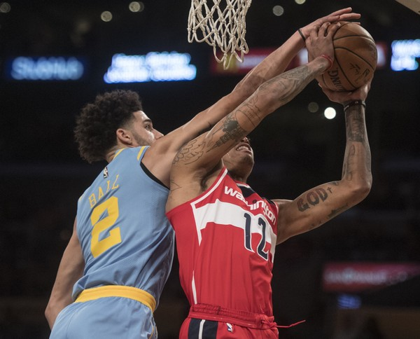 Los Angeles Lakers guard Lonzo Ball, left, blocks the shot by Washington Wizards forward Kelly Oubre Jr. during the first half of an NBA basketball game in Los Angeles, Wednesday, Oct. 25, 2017. (AP Photo/Kyusung Gong)