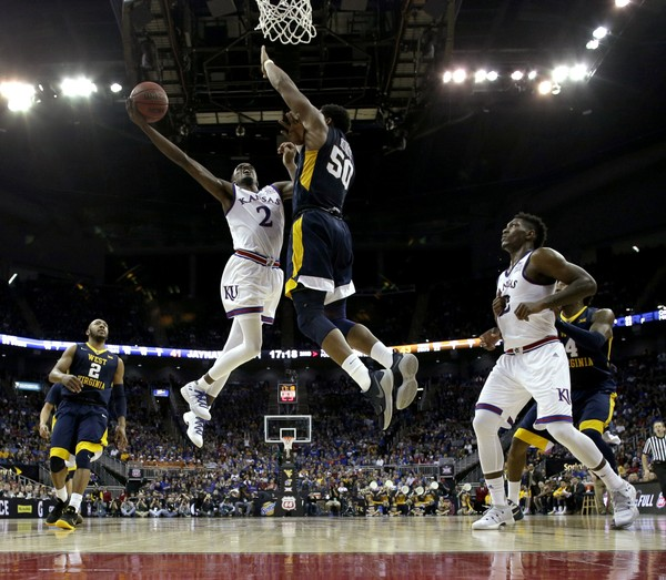 Kansas Lagerald Vick puts up a shot under pressure from West Virginia's Sagaba Konate during the second half of the NCAA college basketball championship game in the Big 12 men's tournament Saturday