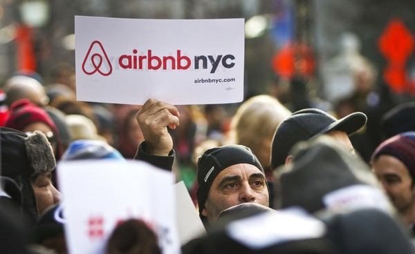 In this Jan. 20, 2015, file photo, supporters of Airbnb hold a rally outside City Hall in New York.