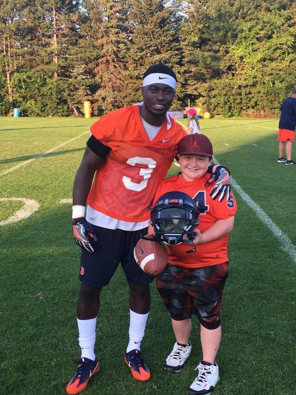 9-year-old Syracuse football fan CJ LaFrance poses with senior inside receiver Erv Philips.
