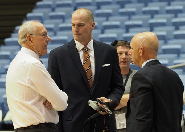ESPN college basketball analyst Jay Bilas (center) chats with Syracuse coach JIm Boeheim and ESPN announcer Sean McDonough. Bilas doesn't think the FBI's probe into college basketball recruiting will change the game.