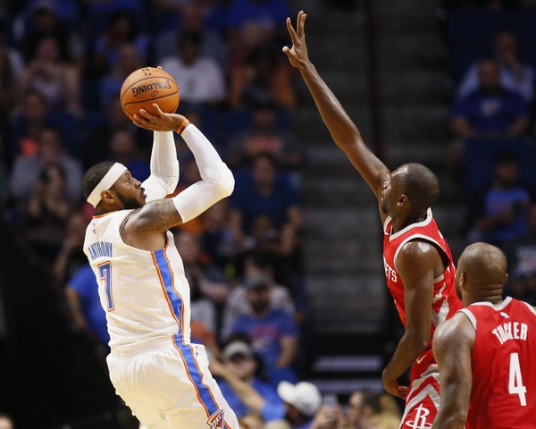 Oklahoma City Thunder forward Carmelo Anthony (7) shoots over Houston Rockets forward Luc Richard Mbah a Moute, center, during the first quarter of an NBA preseason basketball game in Tulsa, Okla., Tuesday, Oct. 3, 2017. (AP Photo/Sue Ogrocki)