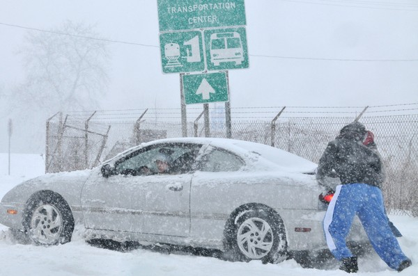 In this 2008 file photo, two good Samaritans help push a woman's car out of a bank of snow on West Bear Street in Syracuse. The state Department of Motor Vehicles urges people to get their cars ready for winter.