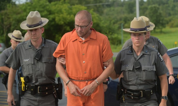 Justin Walters, a Fort Drum soldier, is escorted to his arraignment in the Town of LeRay court on July 10, 2017. He has been charged with murdering Nichole Lum Walters, his wife, and New York State Trooper Joel Davis.