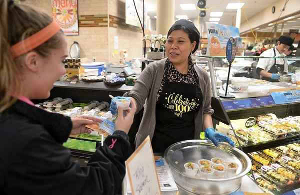 Employee Nan Yi serves customer Maddie Nice, of Baldwinsville, a sample of king salmon roll at the Wegmans Great Northern store at 3955 Route 31 in Clay. Wegmans has been named the top place in retail to work in 2017 by Fortune and Great Places to Work.