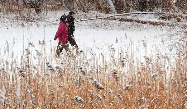 Ruth Florey and Paul Richardson of the Onondaga Audubon Society walk around the Meadowbrook Detention Basin in this 2011 file photo. Light lake effect snow could fall on Friday.
