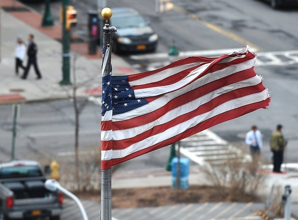 High winds wrap an American flag around a flag pole in Syracuse in this March file photo. Winds of up to 60 mph caused power outages overnight in Upstate New York.