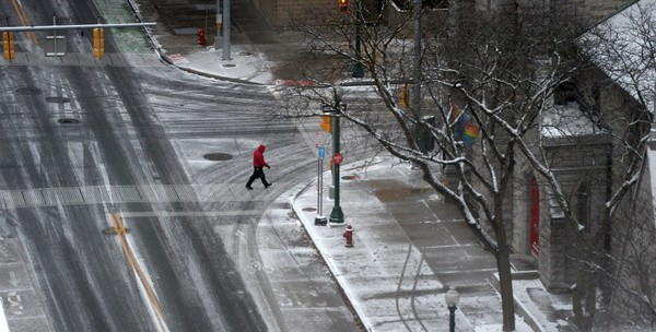 A pedestrian walks across East Fayette Street in downtown Syracuse as a cold winter blast hits Central New York on Nov. 10, 2017.