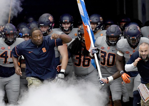 Syracuse football coach Dino Babers rushes out with his players before a game against Wake Forest on Saturday, Nov. 11, 2017, at the Carrier Dome.