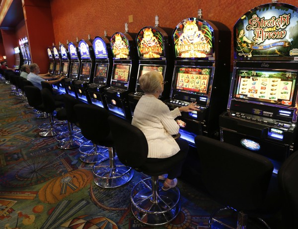 This photo from Thursday, Oct. 16, 2014 photo, show individuals playing video lottery terminals at Tioga Downs, in Nichols, N.Y. Revenues from three new upstate New York casinos have come in far slower than projected, meaning less money shared with local towns, cities and counties.