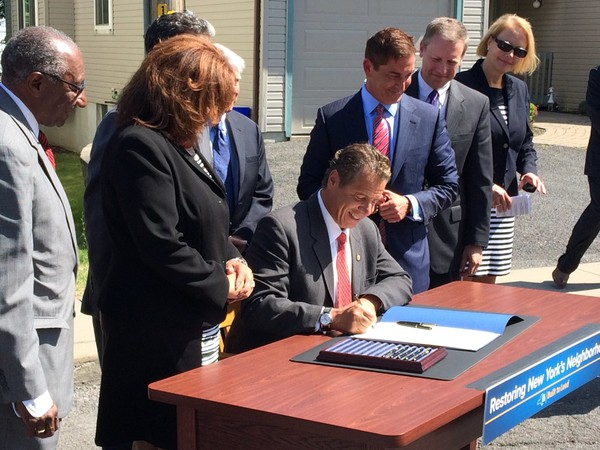 State Sen. David Valesky, second from right, watches as Gov. Andrew Cuomo signs a bill he co-authored giving the state more control over vacant properties held by mortgage banks Thursday, June 23, 2016, on Hazard Street in Solvay. Looking on, from left, were Syracuse Common Council member Van Robinson, state Assemblywoman Pam Hunter, state Sen. Jeff Klein, leader of the Independent Democratic Conference, and Onondaga County Executive Joanie Mahoney.(Tim Knauss | tknauss@syracuse.com)