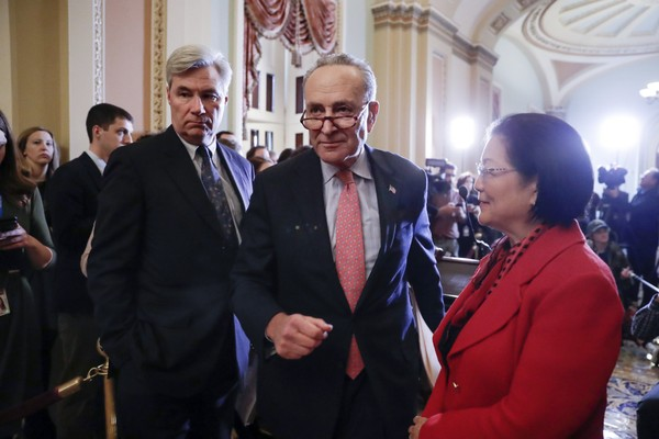 Senate Minority Leader Chuck Schumer, D-N.Y., flanked by Sen. Sheldon Whitehouse, D-R.I., left, and Sen. Mazie Hirono, D-Hawaii, finishes a news conference following a closed-door policy meeting, on Capitol Hill in Washington, Tuesday, Dec. 12, 2017. (AP Photo/J. Scott Applewhite)