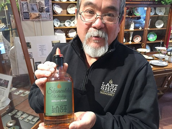 Chris Uyehara, owner and distiller at Last Shot Distillery in Skaneateles, with a bottle of Last Shot's Skaneateles Whiskey, made with a grain called triticale.