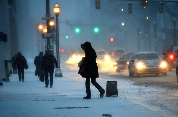 A woman walks through bitter cold and snow across East Fayette Street in Syracuse during evening rush-hour traffic, Jan. 7, 2015.
