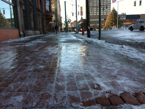 In this file photo, sidewalks in downtown Syracuse are covered with ice. The National Weather Service says ice is possible Friday night as a storm system moves in and temperatures drop.