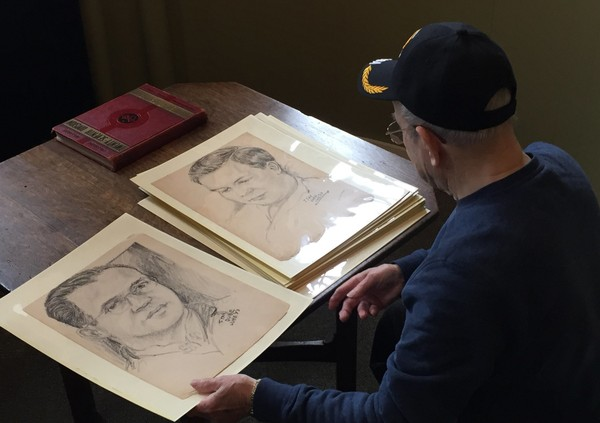 """In this Dec. 8, 2017 photo, World War II veteran Wilfred """"Spike"""" Mailloux looks through a series of sketches of U.S. Army 27th Infantry Division soldiers while visiting the New York State Military Museum and Veterans Research Center in Saratoga Springs, N.Y."""