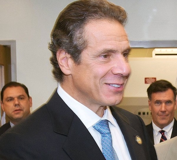 Standing behind Gov. Andrew Cuomo in this cropped 2012 photo are lobbyist Todd Howe, right, and Joseph Percoco, left, a top Cuomo aide. Howe will testify this week in the corruption trial of Percoco and three business executives.(Stephen Sartori)