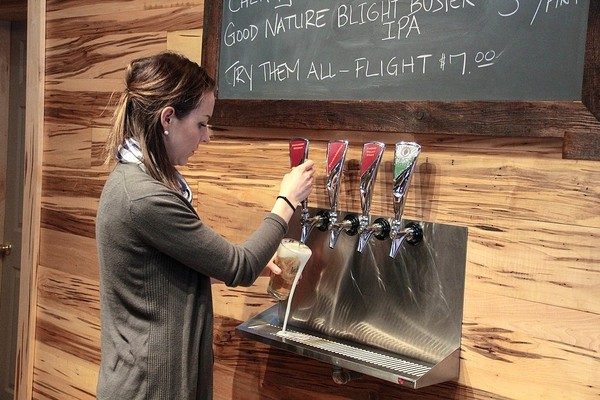 Sammi Clark-Collins, associate director for the Nelson Farms Country Store, pours a beer at the store's 4 Corners Tap Room, 3261 Route 20 in Nelson, Madison County.