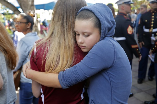 Kaitlynn Cooper, 12, facing, hugs her friend Allison Shonk, 18, a student at Marjory Stoneman Douglas High School, during a vigil at the Parkland Baptist Church, in Parkland, Fla., Thursday, Feb. 15, 2018.  Nikolas Cruz, a former student, was charged with 17 counts of premeditated murder Thursday morning. (AP Photo/Gerald Herbert)