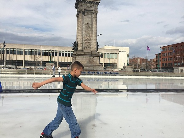 Carter Hines, 9, of Liverpool, skates through melted water atop the ice of the Clinton Square skating rink in downtown Syracuse on Tuesday. Syracuse set a new record high for Feb. 20 of 69 degrees.