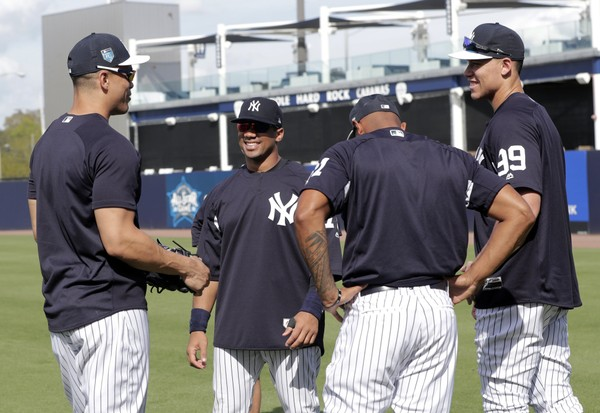 Seattle Seahawks quarterback Russell Wilson, second from left, talks with New York Yankees' Giancarlo Stanton, left, and Aaron Judge (99) before a baseball spring exhibition game against the Philadelphia Phillies, Monday, Feb. 26, 2018, in Tampa, Fla. (AP Photo/Lynne Sladky)