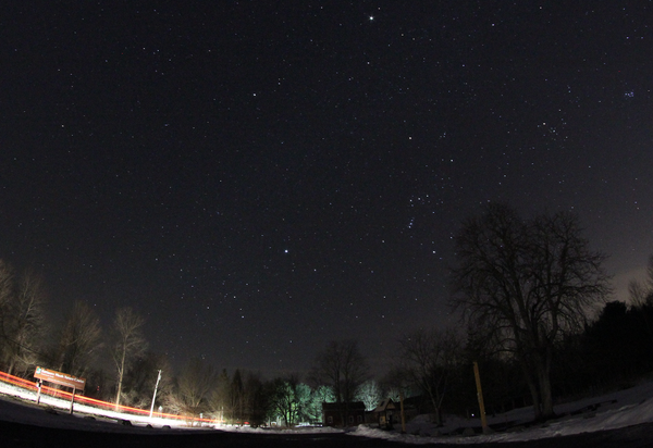 "The best-of-winter constellations over Baltimore Woods in Marcellus, NY. The bright star at lower-center is Sirius in Canis Major. To its right and up, the belt of Orion, the five-star ""V"" of Taurus, and the Pleiades star cluster near the image edge."