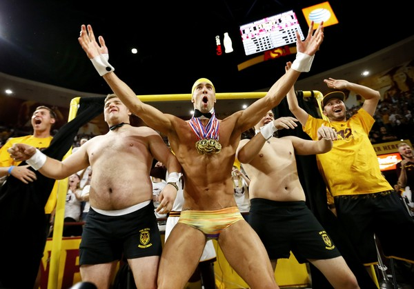 """Olympic swimmer Michael Phelps, center, performs behind the """"Curtain of Distraction"""" during an Oregon State free throw against Arizona State in the second half of an NCAA college basketball game, Thursday, Jan. 28, 2016, in Tempe, Ariz."""
