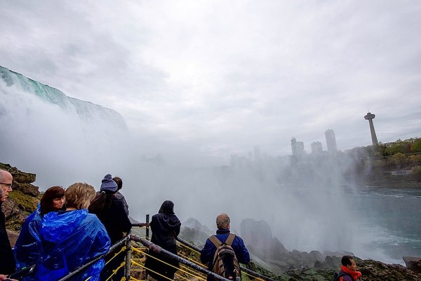 "Tourists in blue ""Maid of the Mist"" ponchos view Niagara Falls from Prospect Point."