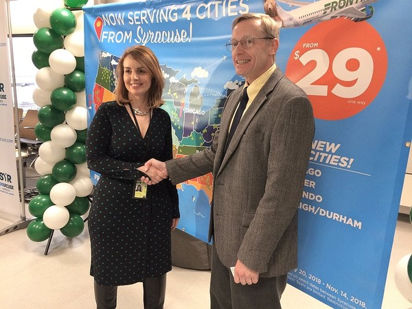 Christina Callahan, executive director of Syracuse Hancock International Airport, and Rick Zeni, chief information officer of Frontier Airlines, shake hands following the announcement Wednesday that the airline will bring its low fares to Syracuse. (Rick Moriarty | rmoriarty@syracuse.com)