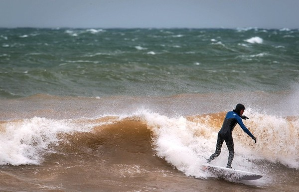 Aurelien Bouche-Pillon braves frigid waters and hurricane-force gusts at Lake Ontario in Putneyville Wednesday afternoon as a cold front with damaging winds blasted Upstate New York.(N. Scott Trimble | striimble@syracuse.com)
