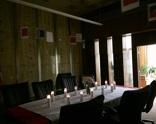 A table is set with 13 candles at the vigil for the victims of the Binghamton American Civic Association shooting.
