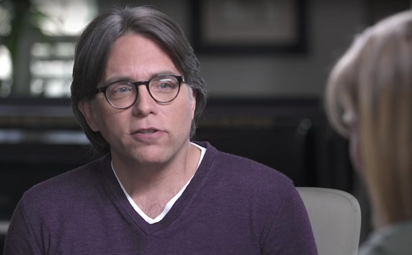 "NXIVM founder Keith Raniere appears in a YouTube video being interviewed by former ""Smallville"" actress Allison Mack, right."